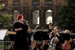 Regina Gowarzewska zapowiadająca koncert, muzycy na scenie