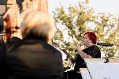 Regina Gowarzewska zapowiadająca koncert, widoczna z perspektywy sceny