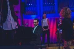 Muzycy na scenie oświetlonej w niebiesko-czerwonych barwach