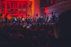Muzycy na scenie oświetlonej w czerwono-pomarańczowych barwach