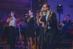 Muzycy na scenie oświetlonej w  fioletowych barwach