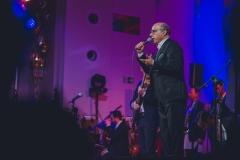Muzycy na scenie oświetlonej w  niebiesko-fioletowych barwach