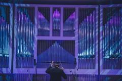 Kolorowo oświetlone organy, dyrygent stojący tyłem