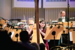 Agnieszka Kaczmarek-Bialic przy harfie na scenie, za nią Orkiestra Symfoniczna Filharmonii Śląskiej