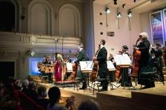 Solistka, dyrygent oraz orkiestra w pozycji stojącej podczas oklasków