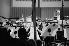 Czarno-białe zdjęcie. Agnieszka Kaczmarek-Bialic przy harfie na scenie, za nią Orkiestra Symfoniczna Filharmonii Śląskiej