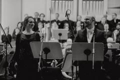 Czarno-białe zdjęcie. Ewa Tracz i Stanislav Kflyuk, w tle orkiestra i chór