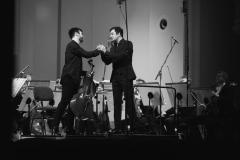 Czarno-białe zdjęcie. Solista Konrad Bargieł na scenie podczas uścisku dłoni z dyrygentem Maciejem Tomasiewiczem