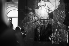 Czarno-białe zdjęcie. Dzieci przy ekranie mgłowym, na którym wyświetlane są postaci z bajek