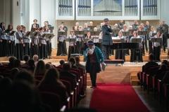 Chór Filharmonii Śląskiej i Jarosław Wolanin na estradzie, w stronę widowni idzie przebrany kolorowo Adam Żaak