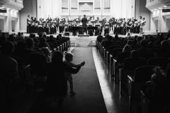 Czarno-białe zdjęcie. Chór Filharmonii Śląskiej i Jarosław Wolanin na estradzie, widoczni z perspektywy widowni