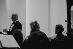 Czarno-białe zdjęcie. Orkiestra i solista Tomasz Rak