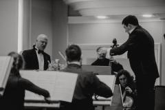 Czarno-białe zdjęcie. Dyrygent, orkiestra oraz solista Tomasz Rak