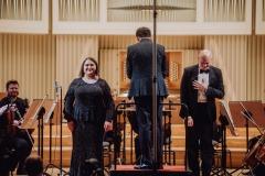 Soliści podczas oklasków, dyrygent stojący tyłem