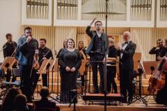 Soliści podczas oklasków, dyrygent stojący przodem do widowni, orkiestra w pozycji stojącej