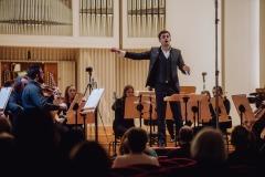 Dyrygent Maciej Tomasiewicz w trakcie koncertu, dyrygujący przodem do widowni