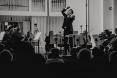 Czarno-białe zdjęcie. Dyrygent Maciej Tomasiewicz w trakcie koncertu, dyrygujący przodem do widowni