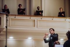 Dyrygent Maciej Tomasiewicz w trakcie koncertu, dyrygujący przodem do widowni, chórzystki ustawione na balkonie bocznym