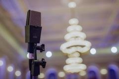 Mikrofon, w tle żyrandole na sali koncertowej