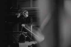 Czarno-białe zdjęcie. Mirosław Jacek Błaszczyk widoczny z perspektywy orkiestry