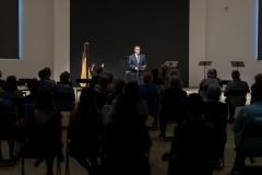 Mężczyzna w garniturze przy mikrofonie - Adam Żaak zapowiadający koncert widoczny z perspektywy widowni