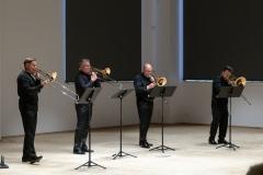 Czterech mężczyzn grających na puzonach (Grzegorz Kurowski, Mateusz Konopka, Marek Przegendza i Piotr Misiak) w eleganckich strojach