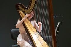Kobieta (Agnieszka Kaczmarek-Bialic) grająca na harfie w eleganckiej sukni