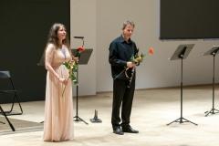 Elegancko ubrani kobieta oraz mężczyzna (Agnieszka Kaczmarek-Bialic i Adam Stachula) stojący na scenie w trakcie oklasków