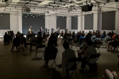 Widok z końca sali - widoczne zaciemnione postaci ludzi zasiadających na widowni. Scena w dalszym planie jest rozmazana.