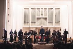 Widok na scenę, orkiestra i dyrygent w pozycji stojącej, zwróceni w kierunku publiczności.