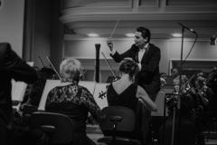 Czarno-białe zdjęcie. Dyrygent Mikhail Tatarnikov, Orkiestra Symfoniczna Filharmonii Śląskiej
